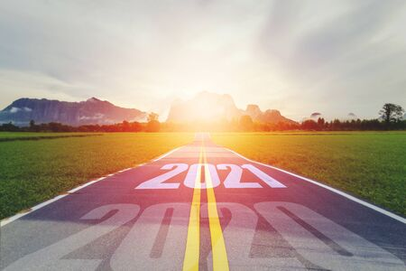 Concept new year With The word 2020 to 2021 Written on The asphalt road in country road Decorate orange light for beauty With With views of rice fields on both sides Concept for new year of 2021