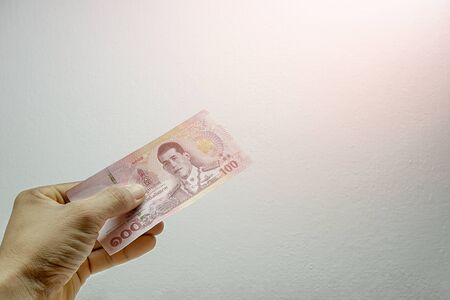A mans hand is holding one 100 bank notes on a white background. Concept Thai baht currency banknote Stock Photo