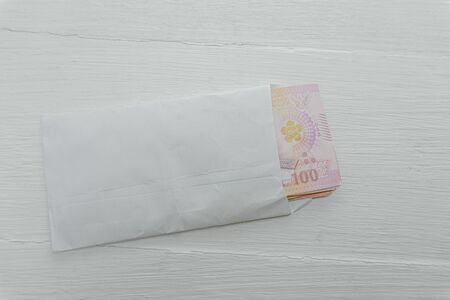 Thai Banknote 100 baht in a White envelope on a white table, Concept of Thai baht currency