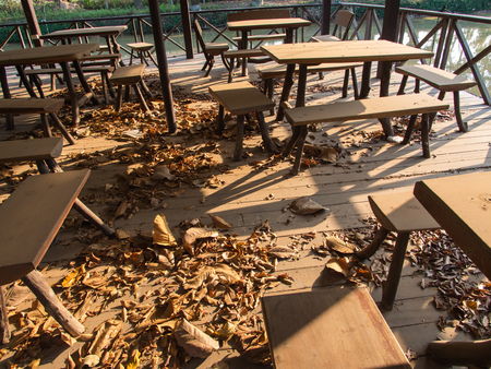 incidence: The Chair on a Wooden Floor with Leaves in Abandoned Restaurant