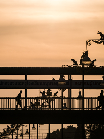 The People Crossing The Footbridge near The Statue of Elephants and Angels Light Posts behind The Sun