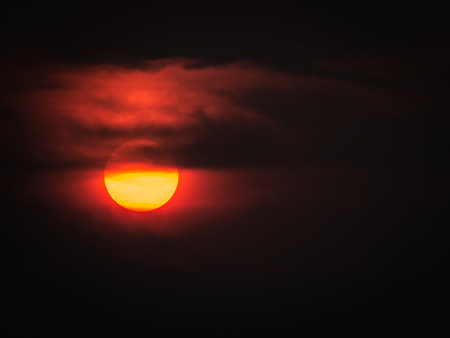 The Fluffy Clouds behind The Yellow Sun in Red Background