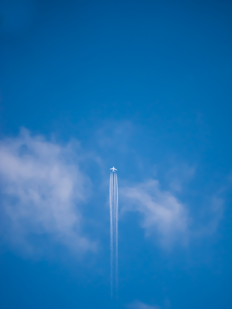 The White Airplane Flying up in The Blue Sky, White Smoke Following The Plane