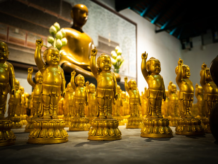 The Buddha Statues in The Children Surround The Modern Art of Golden Buddha Statue Sitting in Chuntawan Temple at Chiang Rai Province Thailand , Architecture Plan in Background Imagens