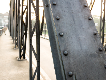 The Beams of The Iron Bridge Lined Long until The Man Walking on The Leaf Imagens