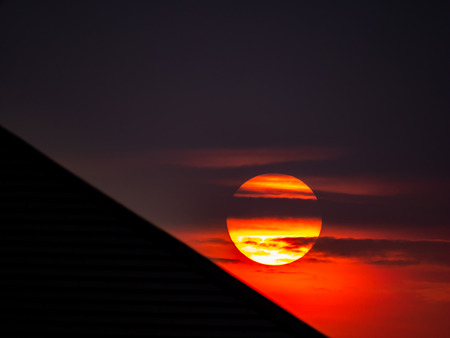 The Yelllow Sun on a Red Background in front of Silhouette Oblique Roof Imagens