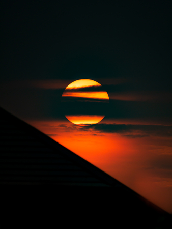 The Yelllow Sun on a Orange Background in front of Silhouette Oblique Roof Imagens