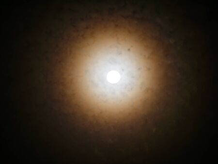 The Moon Shining Through The Clouds as a Radius in The Night