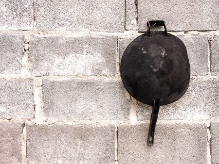 The Old Frying Pan was Burnt Black, Hanging on Te Brick Wall