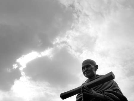 The Somdet Toh Statue Sitting and Holding a Hand Holding Buddhist Scriptures behind The Clouds