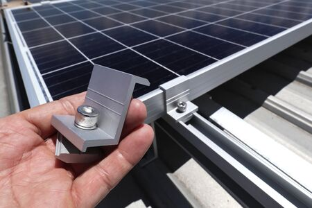 Hand Holding End Clamp of Solar PV Panel with How to Use on Background 스톡 콘텐츠 - 150359419