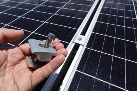 Hand Holding Middle Clamp of Solar PV Panel with How to Use on Background
