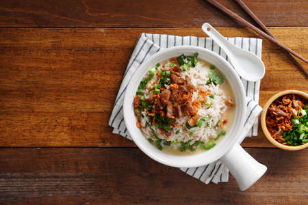 Porridge with spiced pork porridge Garnish with spring onions, coriander, sauteed cabbage, and fried garlic in a baking cup with handle on a wooden table.