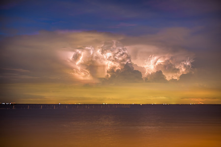 lightening over the rain storm cloud above the sea during twilight photo