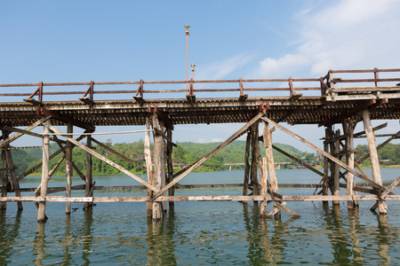 Old wooden bridge across river with bluesky in the back ground photo