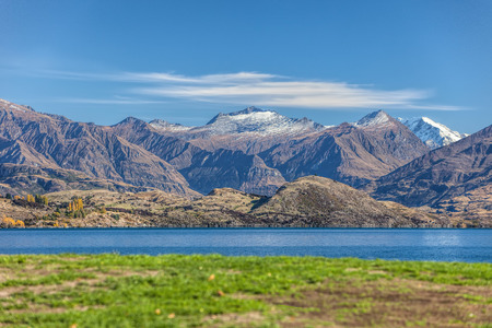 Lake Wanaka in autumn colors with green grass in the foreground. photo