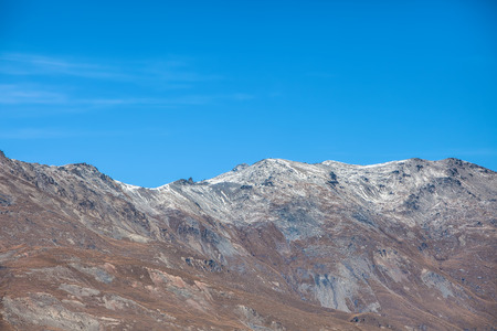 Mountain range with few snow on the top at crown range road , New zealand photo