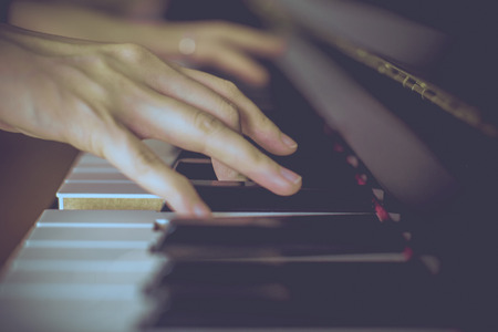piano lesson: Lady playing piano with vintage look Stock Photo