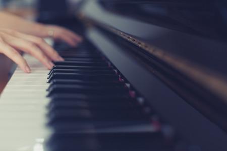 tocando el piano: Señora que juega el piano con mirada de la vendimia