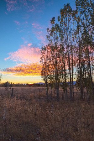 colorful cloudscape: Sunrise behind grass land with clear colorful sky and nice cloudscape above