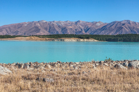 Turquoise lake near Twizle town, New Zealand, with mountain range and blue sky in the back ground photo