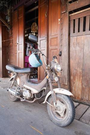 amphawa: An old scooter parked along the side walk in small vilage, Amphawa, Thaialnd Stock Photo