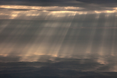 arial views: Beams of light through cloudy sky. The photo was taken from an aircraft flight from Vienna to Croatia
