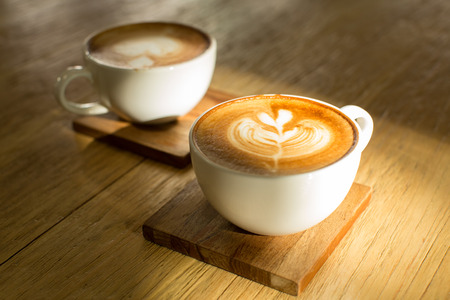 Two hot latte on wooden saucers and table photo