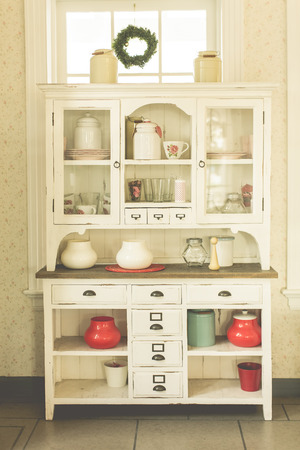 wooden shelf: Antique kitchen cabinet and old style kitchen ware in pastel look Stock Photo