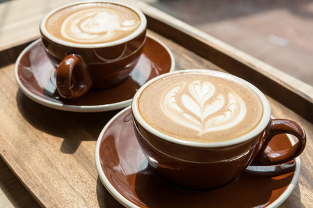 Two hot latte on wooden tray and table with selective focus on the latte art Stock Photo