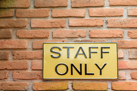 Yellow Staff only warning sign on retro style brick wall photo