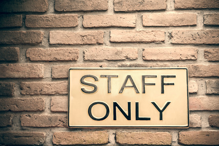 Yellow Staff only warning sign on retro style brick wall with vintage and grunge look photo