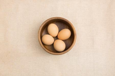 huevo: Huevos crudos en un cuenco de madera de teca con fuera de fondo blanco pa�o