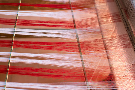 Weaving equipment with woven yarn in the background