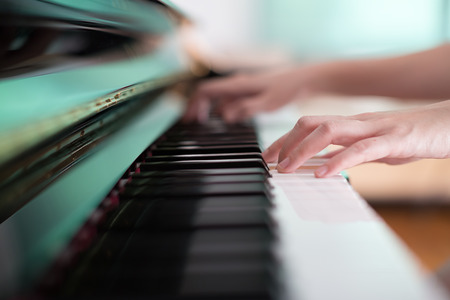 piano closeup: Lady playing piano with selective focus and shallow depth of field.