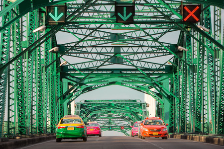 taxicab: Bangkok, Thailand- June 20, 2015: Colorful taxicab running across the Memorial bridge, the oldest bridge that cross Chao Phraya river, in the early morning.