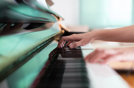 Lady playing piano with selective focus and shallow depth of field.