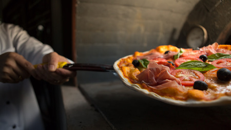 Chef put parma ham pizza in to clay stove at Italian restaurant.
