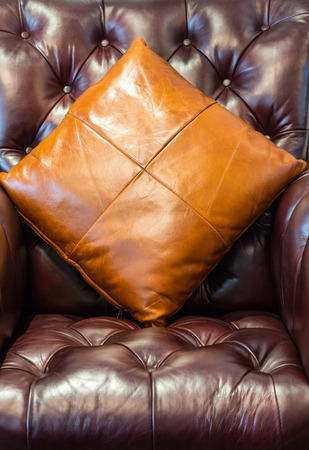 throw cushion: Leather sofa and pillows in retro tone with selective focus on the pillows