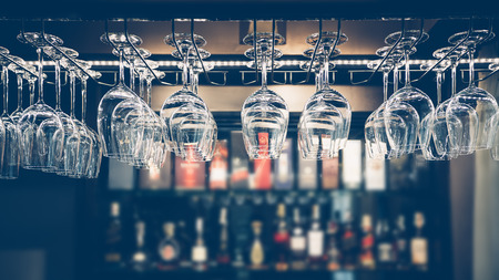 liquors: Empty glasses for wine above a bar rack in vintage tone. Stock Photo