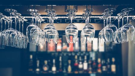 Lege glazen wijn boven een bar rack in vintage toon.