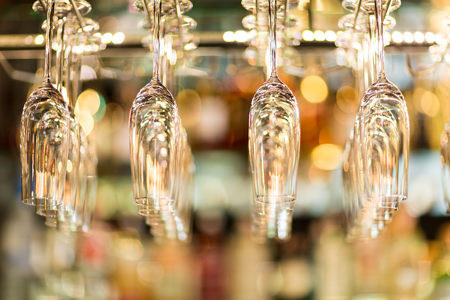 Hanging champagne glasse on a rack above liquor counter lit by led and down lights with selective focus and very tiny depth of field.