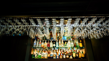Hanging glasses on a rack above liquor counter lit by led and down lights with selective focus in dark tone.