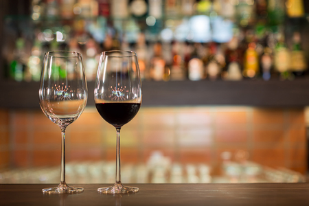 bar top: Two tall wine glasses on top of a wooden bar counter in side a restaurant. Stock Photo