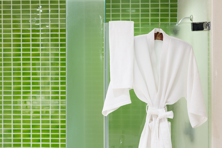 shower: White bathing gowns hanging on glass shower box with green tiles wall Stock Photo