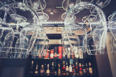 down lights: Hanging brandy glasses on a rack above liquor counter lit by led and down lights with selective focus and vintage blue tone. Stock Photo