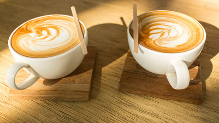 saucers: Two hot latte on wooden saucers and table