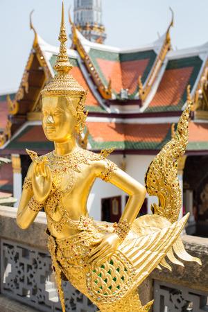 mahabharata: Beautiful Golden kinnari , half- human half-bird character in Mahabharata, at Wat Phra Kaew, Bangkok, Thailand