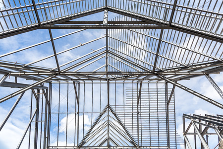 roof framework: Roof frame of business building under construction against blue sky.