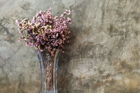 Dry flower in tall and transparent vase with old cement wall in the background in retro looks.